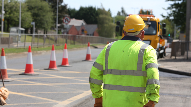 A roads worker at a road coned off for improvements