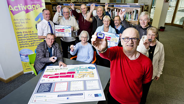 A group of mall walkers show off their steps on their pedometers as they gather at East Kilbride Central Library