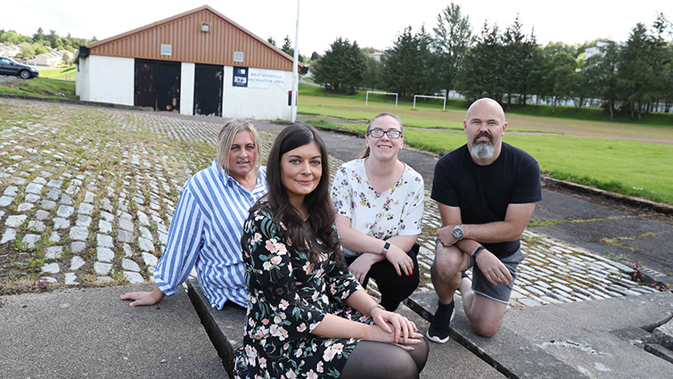 Sian Flynn from the community engagement team sits with three members of the Friends of Westwoodhill group in front of the local sports pavilion.