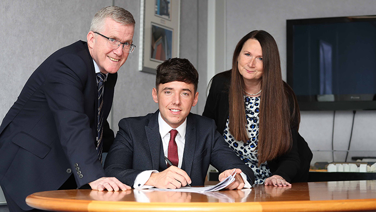 In this photograph from left to right is South Lanarkshire Council (SLC) Executive Director of Housing and Technical Resources Daniel Lowe, Chair of Housing Councillor Josh Wilson who is seated at a desk and Head of Housing Annette Finnan