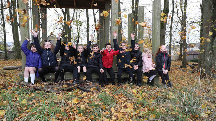 Ten pupils aged 5-11 sit in a line on a raised stage area in the school woodland throwing leaves in the air.