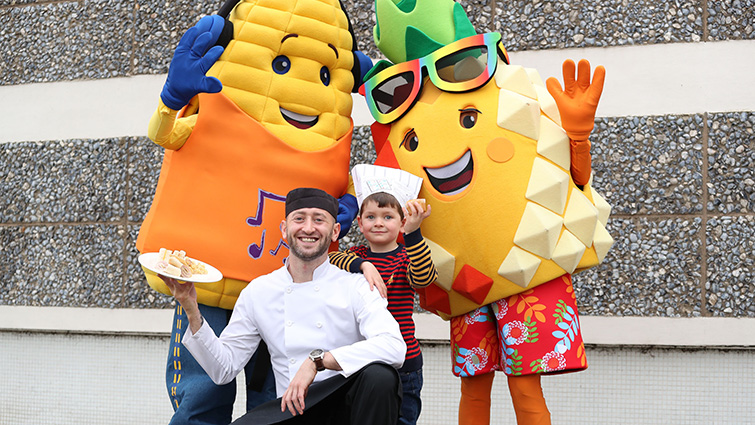 One of the nursery pupils from the taste and try sessions poses with SLC's Go Fresh characters and the chef who prepared the taster menu