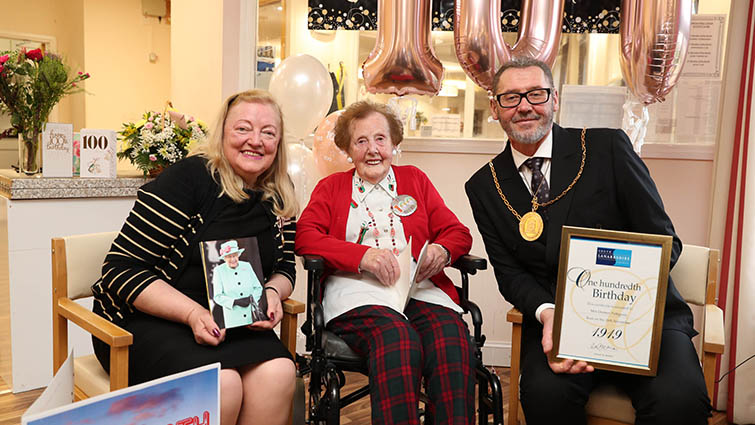 Mrs Pettigrew wearing tartan trousers and a red cardigan sits between Provost McAllan on her left and Deputy Lieutenant Margaret Morton on her life, each holding their gifts to her.