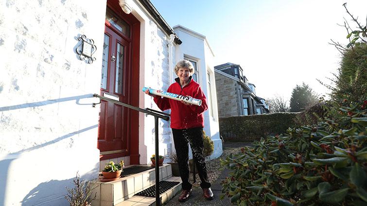 Helen Biggins of Seniors Together, herself and older resident of South Lanarkshire, stands on her doorstep spreading the salt from her salt stick on her steps and path.