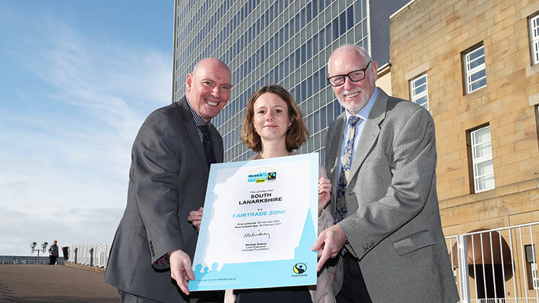 Chief Executive Cleland Sneddon, Food policy officer Helene Gourichon and Council Leader, John Ross are standing together on the steps of council headquarters with an enlarged version of the council's Fairtrade certification.