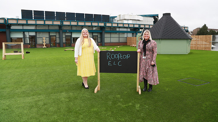 A woman in a yellow dress stands to the left of a chalkboard to the right of it there is a second woman in a paisley pattern dress. They are standing in the outdoor play area at Rooftop ELC East Kkilbride