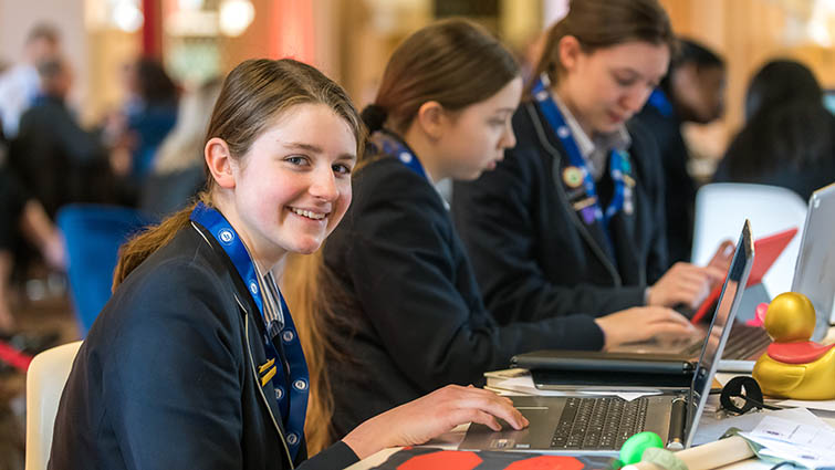 One girl smiles to the camera, alongside two friends who are working together on their cyber project. All are wearing blue school blazers and looking at laptops.