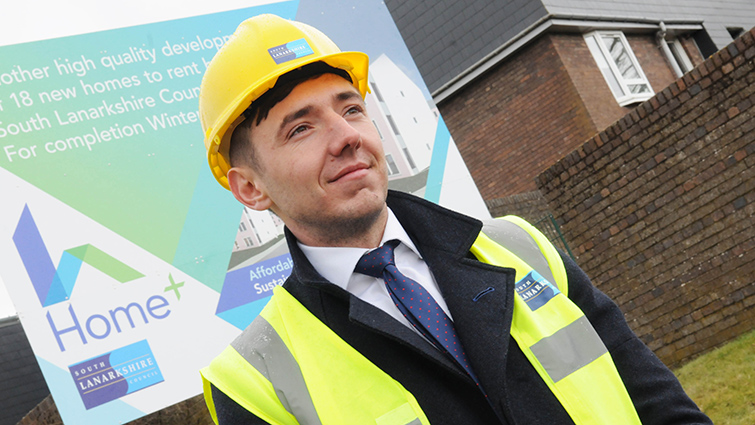 This is a picture of Councillor Josh Wilson South Lanarkshire's Chair of Housing and Technical Resources. He is wearing a safety helmet and hi-vis vest