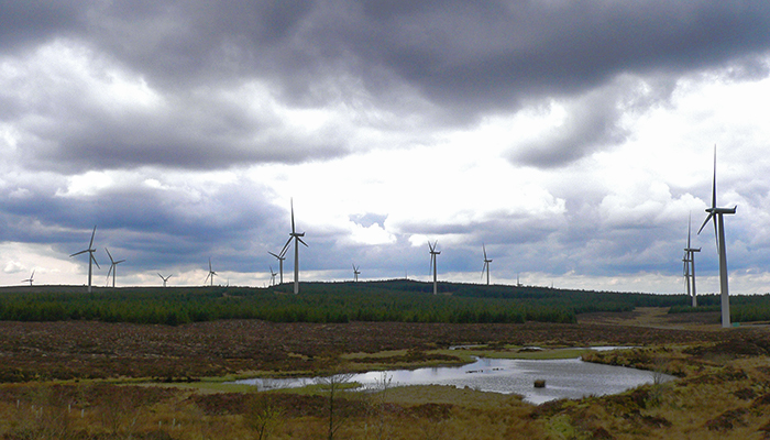 This is a photograph of the Whitelees Wind Farm taken from Ardochrig Hill in the foreground there is a small loch behind it there are a number of wind turbines standing in moorland