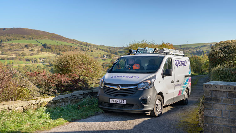 This is a picture of a wide van with  Openreach livery it is on a rural road with bushes to either side.