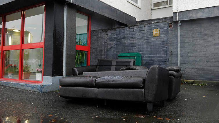 A discarded couch sits outside a block of high-rise flats in South Lanarkshire