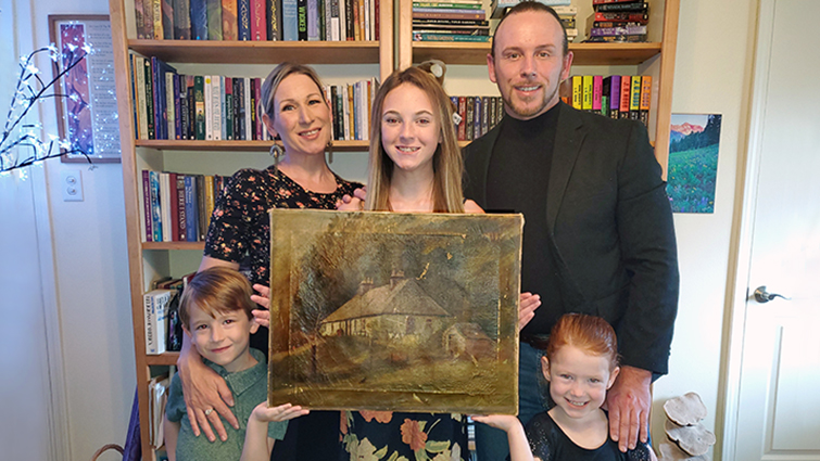 This is a picture of James Rawlings, who is standing at the back on the right, with his wife, at the back left, and children at the centre of the family group his daughter is holding the painting The Hoolet Raw