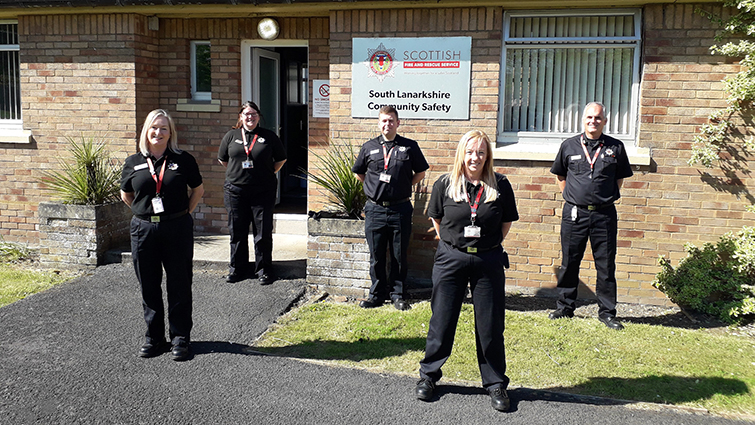 This is a picture of five members of the Scottish Fire and Rescue Service Community Action Team in South Lanarkshire they are standing in front of a brown brick building.