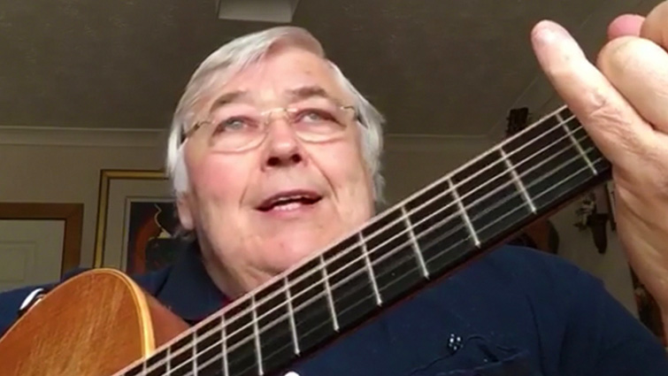 This is a head and shoulders photograph of a man playing guitarthe neck of the guitar is extending into the foreground with his hand on it in the top right corner of the frame.