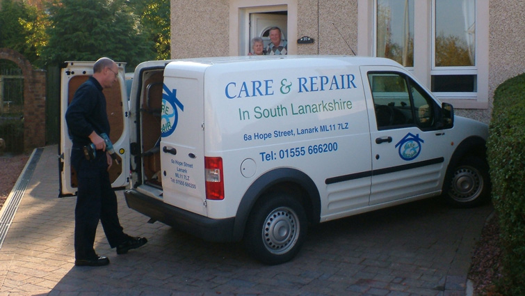 A volunteer from the Small Repairs Service with his van at the house of an elderly couple to offer assistance.