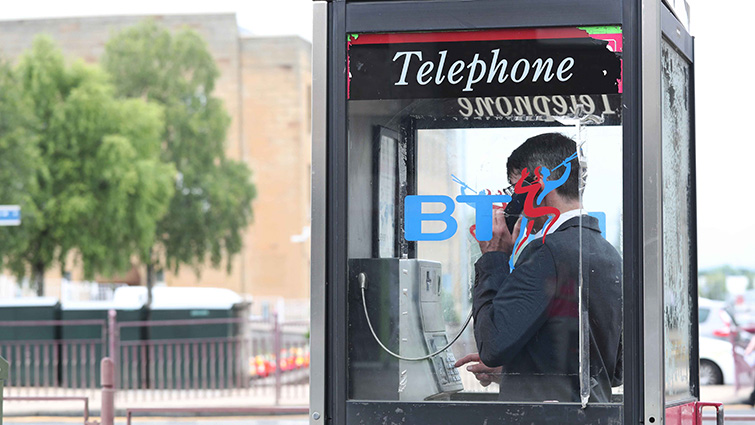 Payphone in use in Hamilton