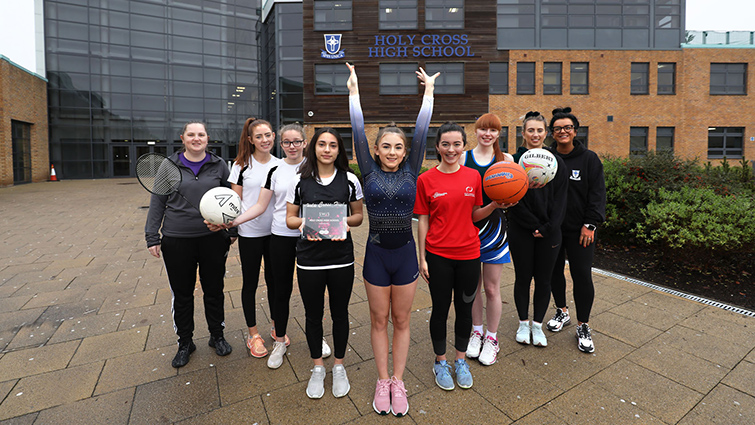 Five Holy Cross High female pupils in front of the school wearing the sports outfits that represent the school in badminton, gymnastics, netball, football and athletics. Young athlete Caterina Nelli holds the aware with teachers either side