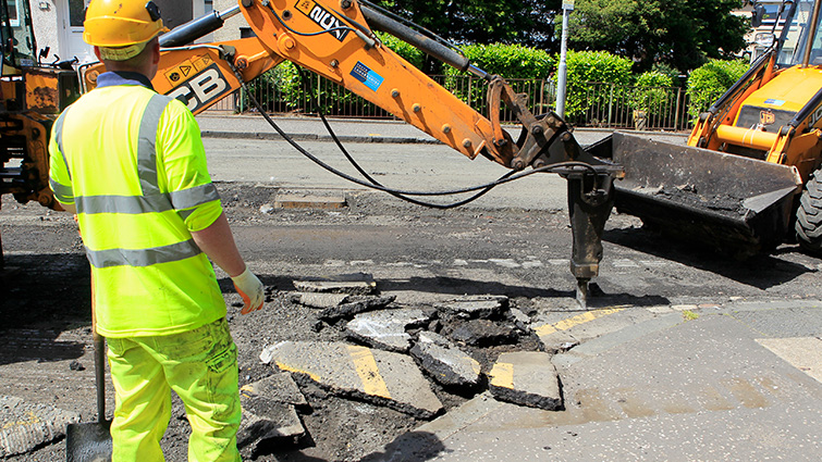 A council worker looks on as a machine breaks up the existing surface to prepare the road for resurfacing