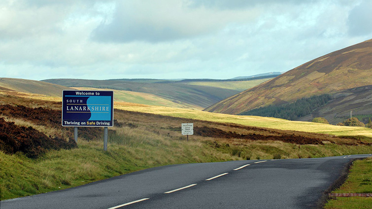 This is a picture of a rural road in the hills in Southern South Lanarkshire, to the left of the picture is a blue sign that reads welcome to South Lanarkshire, thriving on safe driving.