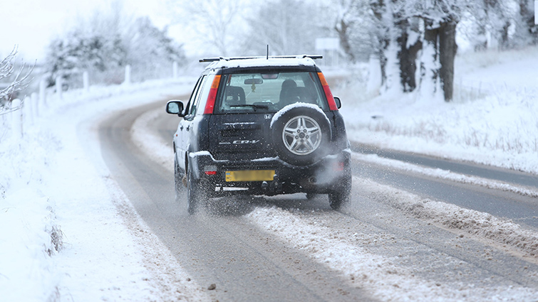 A car makes its way down a South Lanarkshire road following snow