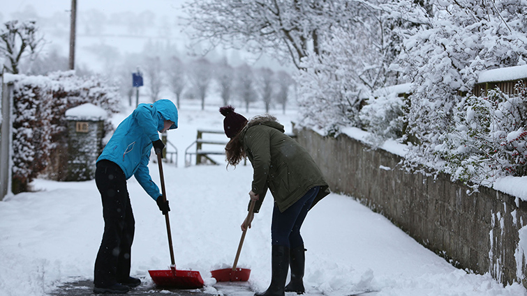 Two people clearing snow from their path in South Lanarkshire