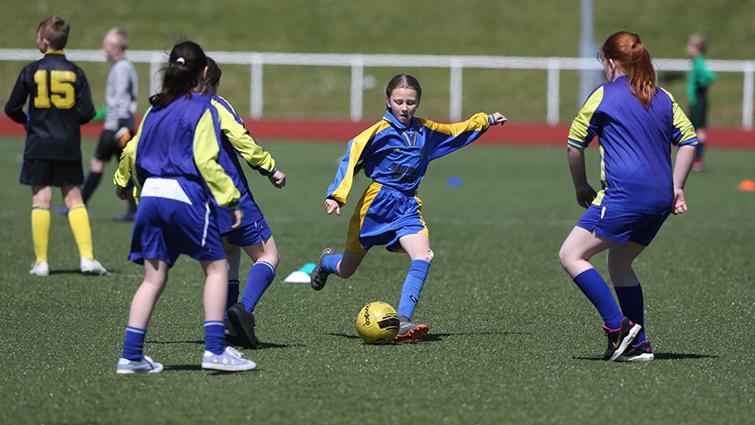 Image shows girls playing football at John Cumming Stadium, Carluke