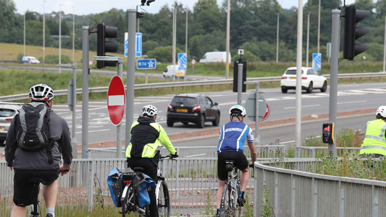 Four cyclists on the new walking and cycling path at the Raith interchange the M74 can be seen in the background.