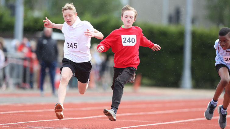 This is a picture of two boys crossing the finish line in a 100m race the boy on the left is wearing a white t-shirt and the one on the right is wearing a red long-sleeved top.