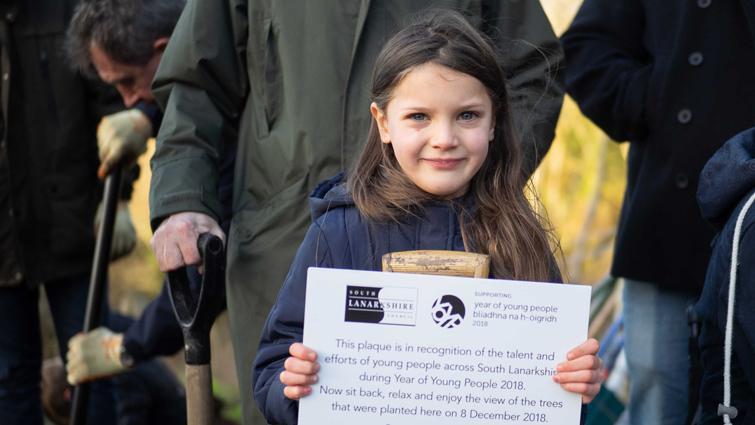 This is a picture of a young girl holding a plaque that records a tree planting ceremony held in Chatelherault Country Park to mark the end of the Scottish Year of Young People
