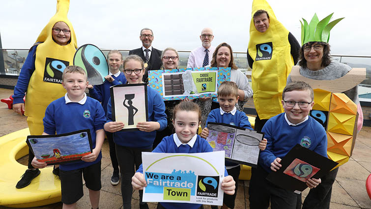 A group of six pupils from Biggar Primary School, with members of the town's Fairtrade Steering Group, Provost Ian McAllan and two men dressed as life sized bananas, show off the town's Fairtrade Directory.