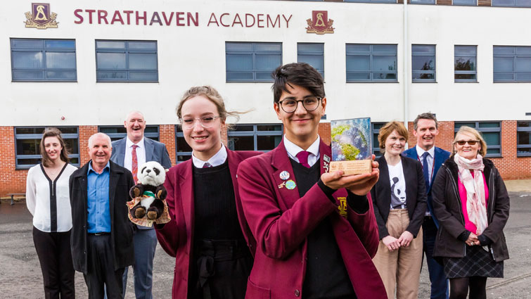 Two Strathaven pupils in uniform stand in the foreground holding the award and the WWF toy panda logo. Lined up behind them are councillor John Anderson, two reps from WWF, Headteacher Kevin Boyd and the council's Julie Richmond.
