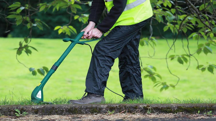 This is a picture of a man in a hi-vis vest trimming the edge of a lawn with a strimmer